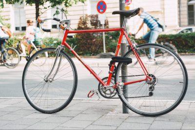 Ein rotes Rennrad an ein Straßenschild gelehnt. Im Hintergrund drei Radfahrer.