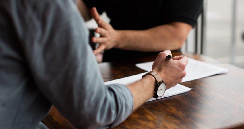 zwei Männer in einer Besprechungssituation an einem Tisch