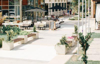 eine moderne Fußgängerzone mit angrenzendem Café im Sommer