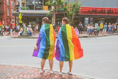 zwei Frauen eigehüllt in Regenbogenfahnen stehen an einer belebten Kreuzung