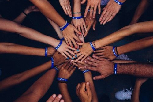 Diverse Menschen recken ihre Hände in die Mitte des Bildes