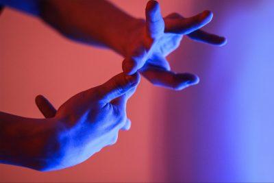 Zwei Hände formen eine Gebärde, im Hintergrund rot-blaues Licht