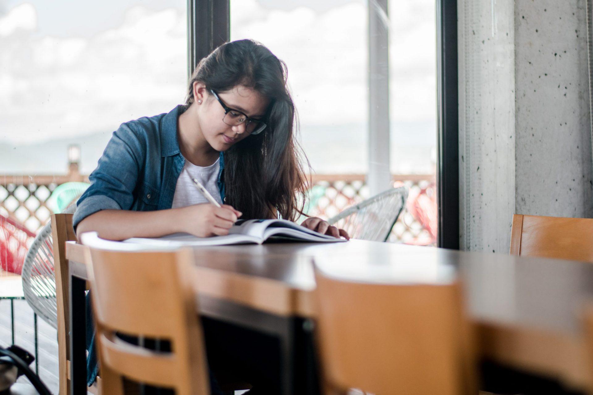 Eine Fraus sitzt an einem Tisch und arbeitet in einem Studienbuch