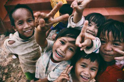 Sechs Kinder aus armen Verhältnissen schauen fröhlich in die Kamera