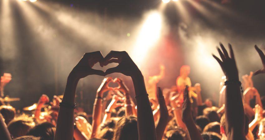 Publikum eines Konzertes von hinten aufgenommen, erhobene Hände zeigen ein Herz
