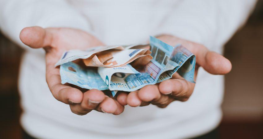 ein Mensch hält einige Euro-Banaknoten in den ausgestreckten Händen
