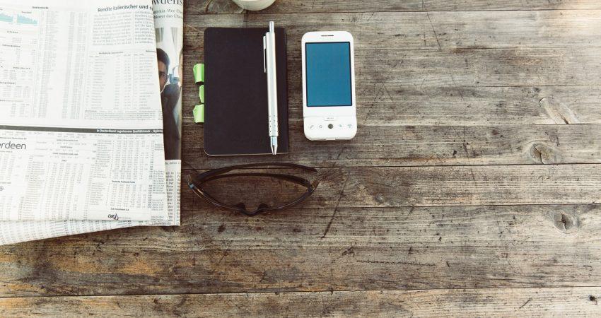 Blick auf einen rustikalen Tisch mit Zeitung, Notizbuch, Mobiltelefon und Sonnenbrille und einer Tasse Kaffee.