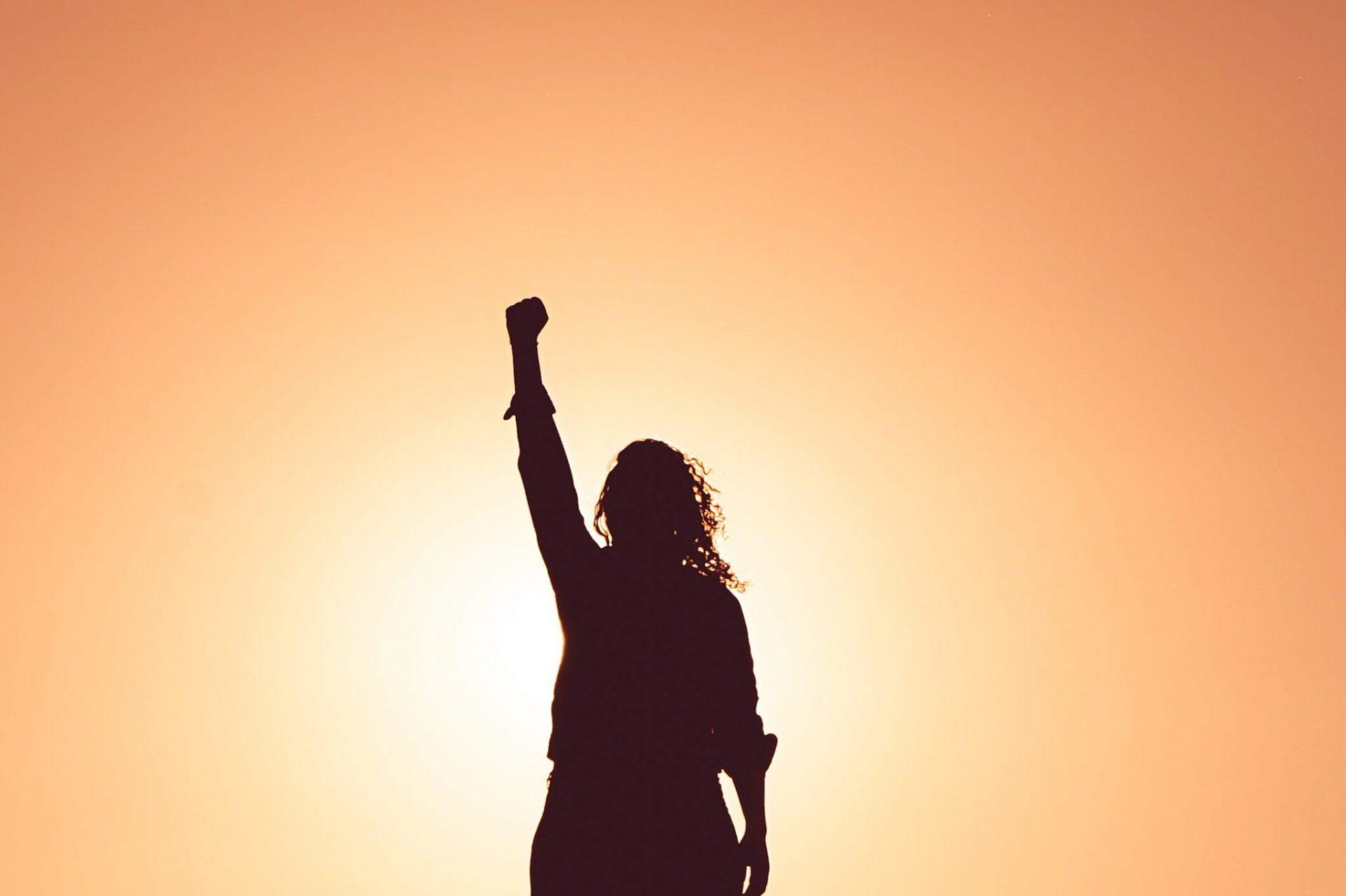 Eine Frau im Sonnenaufgang reckt die Faust in die Höhe
