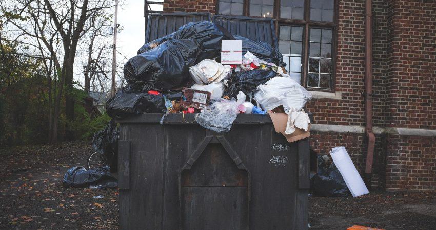Ein überfüllter Müllcontainer vor einem Backsteingebäude.