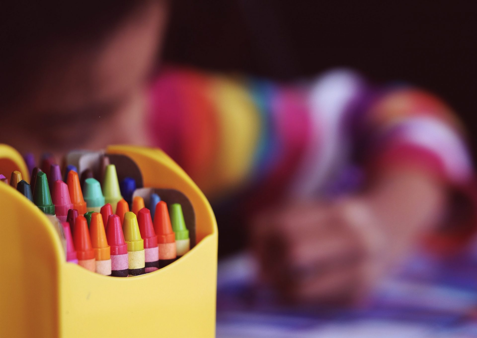 Bunte Wachsmalkreiden in einer offenen Packung, im Hintergrund unscharf ein malendes Kind