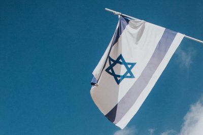 Eine israelische Flagge weht im Wind, im Hintergrund blauer Himmel