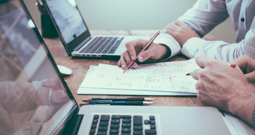 Zwei Menschen sitzen an einem Tisch vor zwei Laptops, sie skizzieren geeinsam etwas auf einem Notizblock
