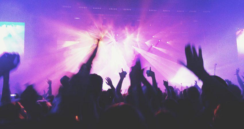 Schemen feiernder Menschen auf einem Konzert, die Szene ist in lila Licht getaucht.