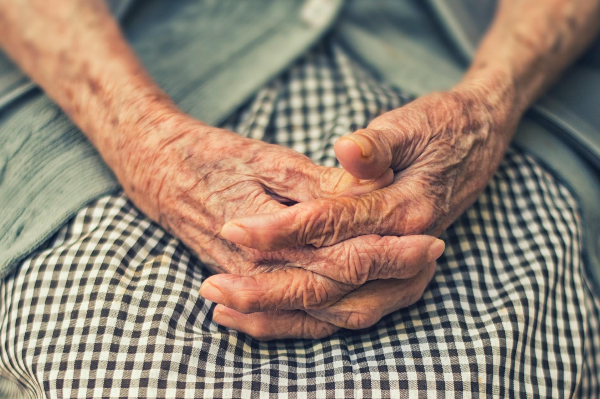 Eine Seniorin hat ihre ände gefaltet in den Schoß gelegt.