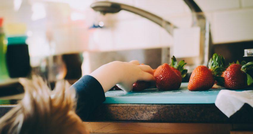 Ein Kind greift nach Erdbeeren, die neben dem Spülbescken auf einer Küchenanrichte liegen