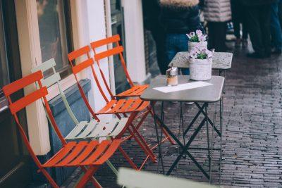 Metallklappstühle und kleine Tische auf Kopfsteinpflaster vor einem Café.