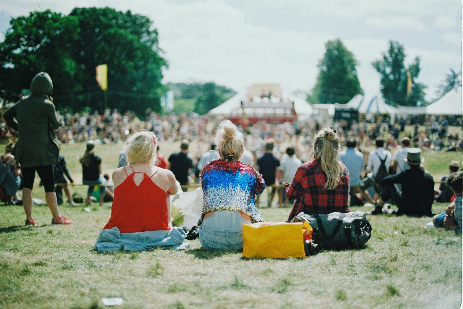 Drei Frauen sitzen nebeneinander auf einer Wiese während einer sommerlichen Festival-Veranstaltung