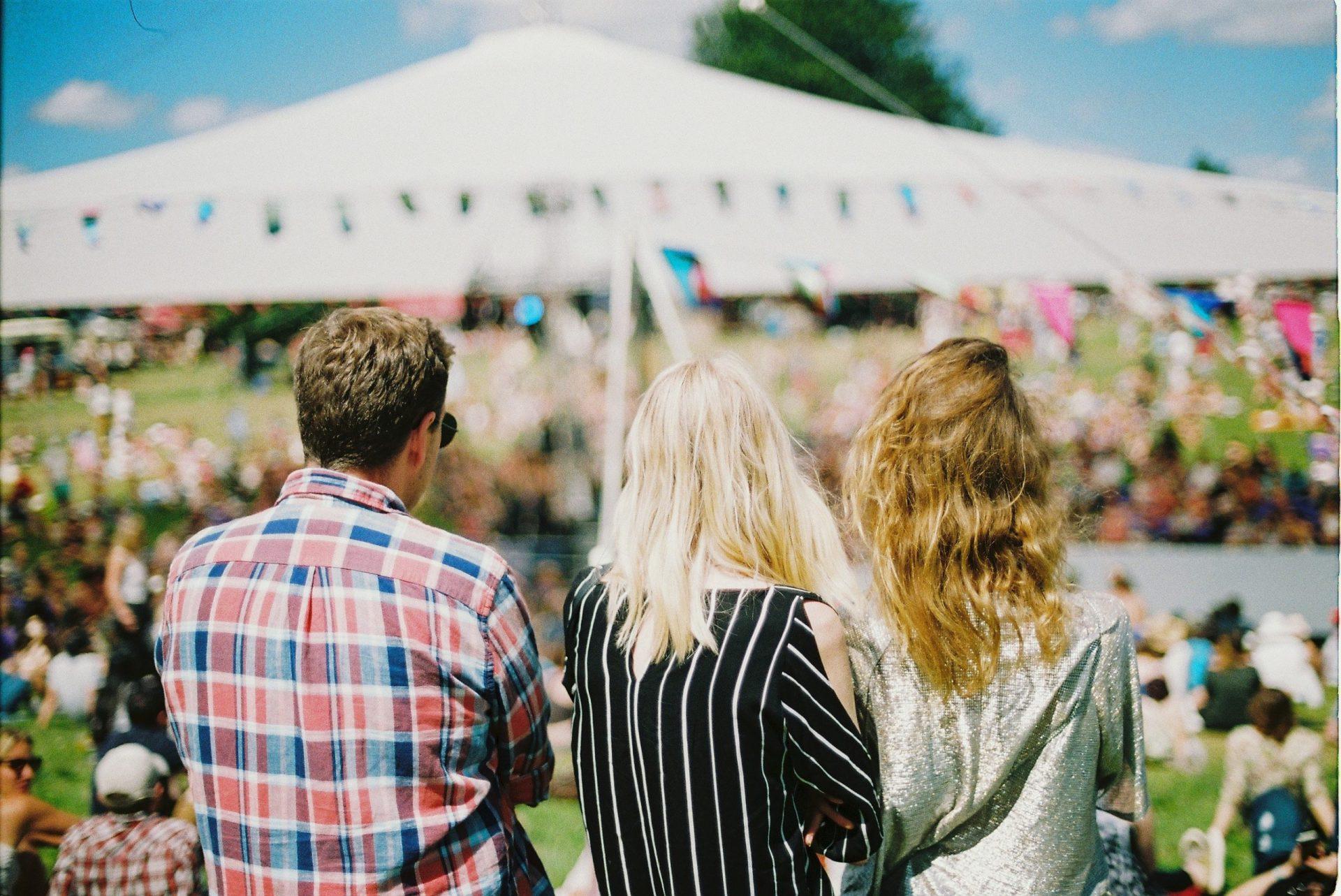 Drei Menschen, die auf ein sommerliches Festival blicken.