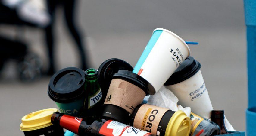 Ein von Einweg-Kaffeebechern überfüllter öffentlicher Mülleimer.