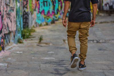 Ein Mensch läuft neben einer mit Graffiti verzierten Mauer einen Gehweg entlang