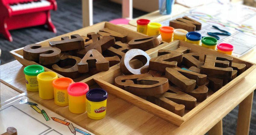 Holzbuschstabe-Bausteine und bunte Knete auf einem Kindertisch