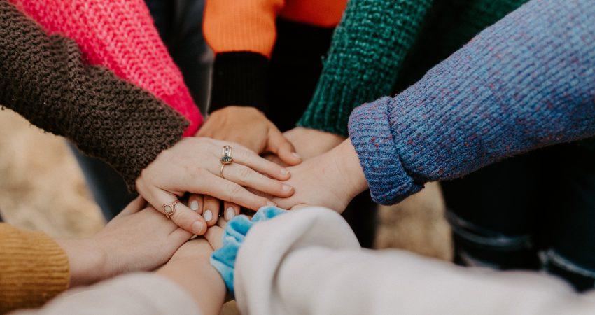 Acht Menschen in bunten Pullovern legen die Hände in der Mitte des Bildes aufeinander