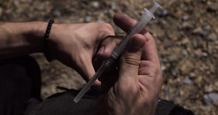 Ein Mensch hält eine Spritze in den Händen.
