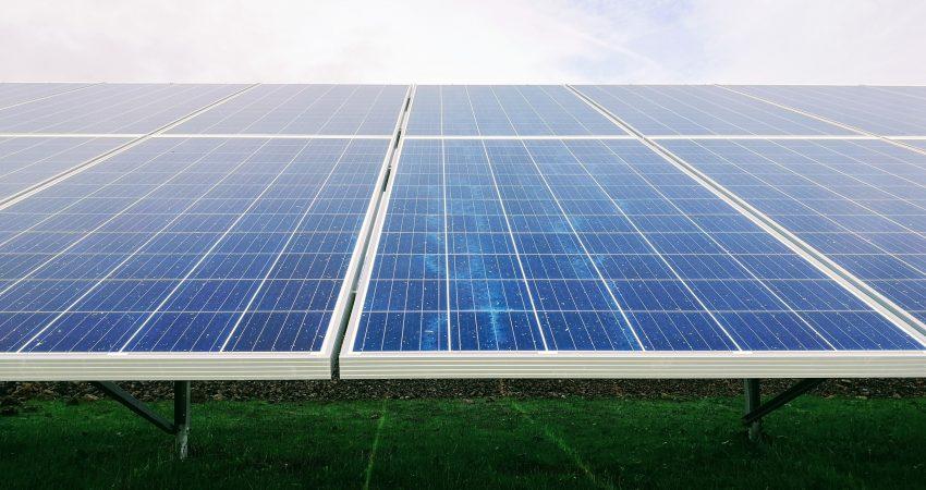 Photovoltaik-Anlge auf einer grünen Wiese im Sonnenschein, im Hintergrund freundlicher Himmel