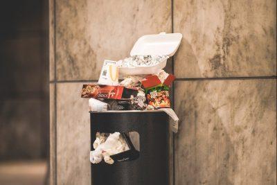 Ein überfüllter öffentlicher Mülleimer vor einer Mamorwand.