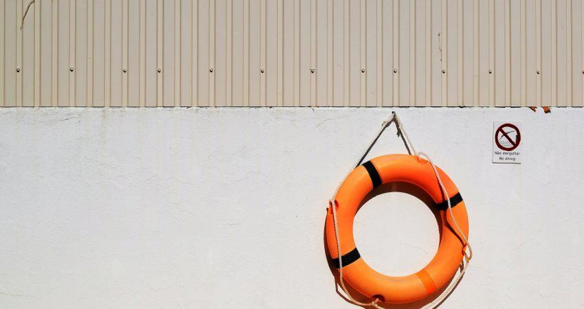 Ein orangener Rettungsring, der an einem Haken an einer Wand hängt.