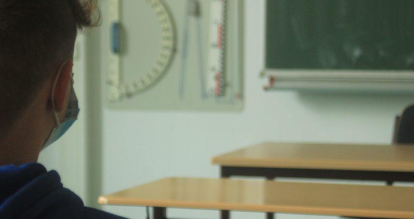 Ein Jugendlicher mit OP-Maske sitzt in einem Kalssenzimmer und sieht zur Tafel