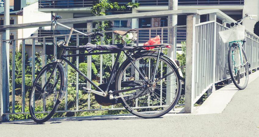 Ein Fahrrad, das an ein Brückengeländer gelehnt ist.