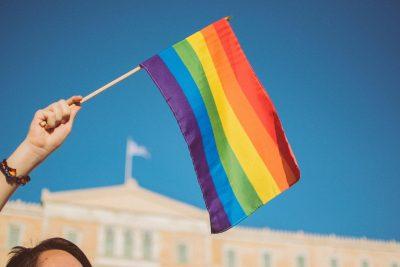 Ein Mensch schwenkt ein Regenbogenfähnchen, im Hintergrund ein Gebäude und blauer Himmel