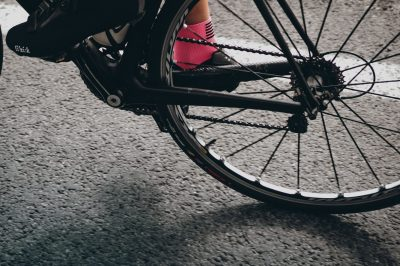 Hinterrad, Kette und Pedale eines Rennrades auf Asphalt