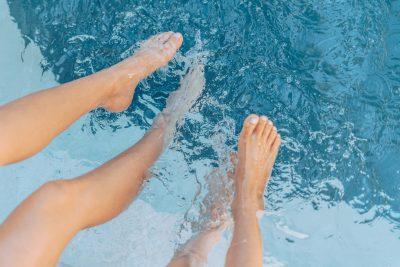 Zwei Menschen strecken die nackten Beine in ein Schwimmbecken.