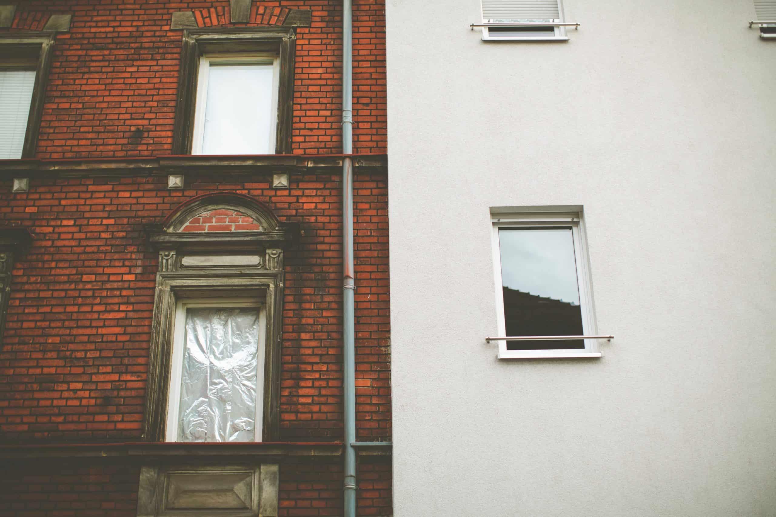 Fassade eines Backstein-Altbaus direkt angrenzend an die Fassade eines sanierten Hauses