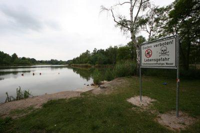 """Der Silbersee Nürnberg vor einem bewölkten Himmel, im Vordergrund das Warnschid """"Baden verboten! Lebensgefahr""""."""