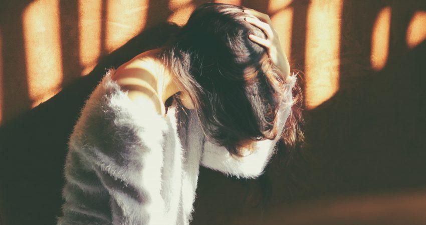 Eine Frau mit gesenktem Kopf und der Hand in den Haaren.