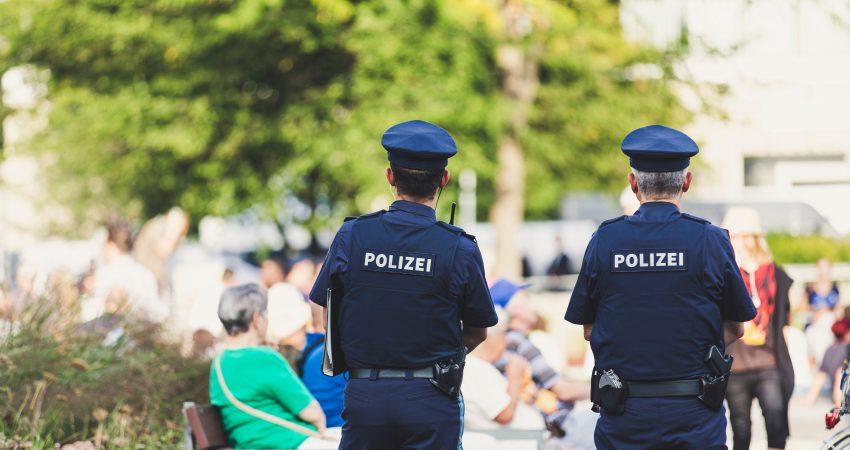Zwei Polizisten beaobachten einen belebten öffentlichen Platz.