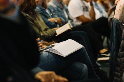 Menschen in einem Seminarraum sitzen in Reihen, teilweise haben sie Notizbücher auf den Knien.