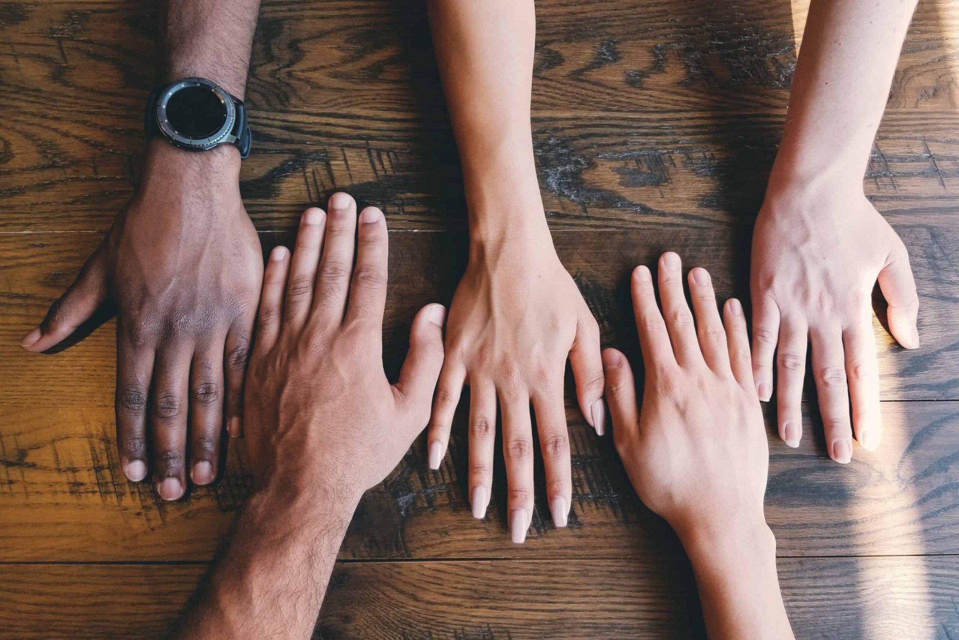 Verschiedene Menschen legen ihre Hände auf einen Tisch