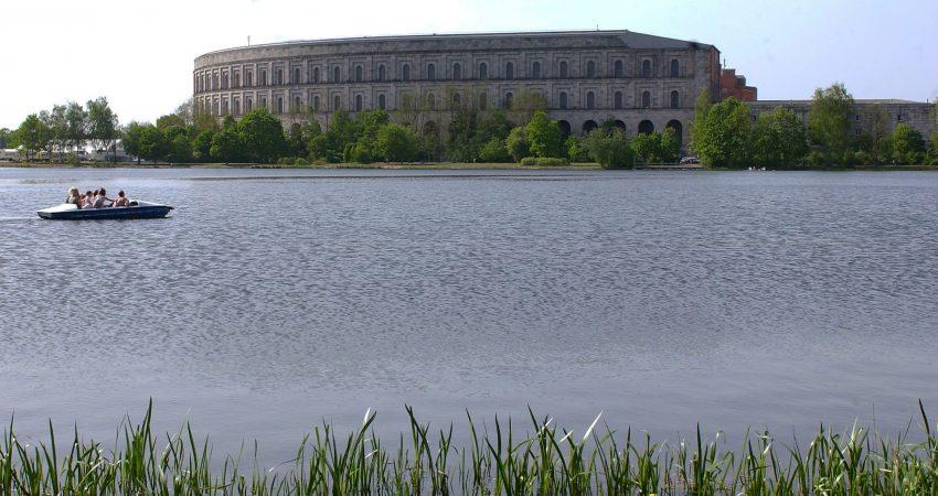 Die Kongresshalle Nürnberg, im Vordergrund der Dutzendteich und eine Gruppe Menschen in einem Tretboot.