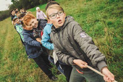 Teenager und Kinder beim Seilziehen