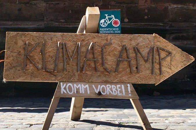 """Schild mit der Aufschrift """"Klimacamp - Komm vorbei!"""""""