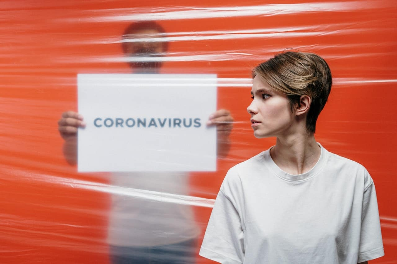 """Besorgte Frau blickt auf ein Schild mit der Aufschrift """"Coronavirus""""."""