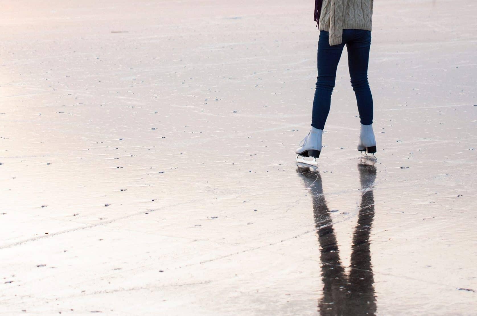 Eine Person auf Schlittschuhen auf einem zugefrorenen See.