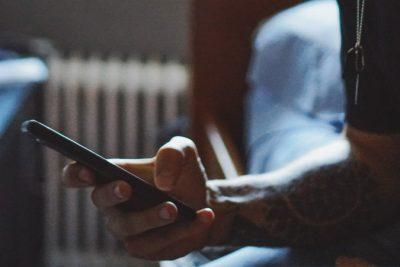 Jemand hält ein Mobiltelefon in der Hand