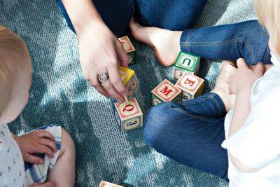 Zwei Kinder spielen mit bunten Holzbauklötzen, auf denen Buchstaben zu sehen sind