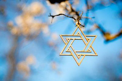 Ein Davidstern-Anhänger hängt an einem Zweig vor blaum Himmel