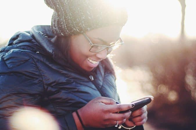eine Frau schaut auf ein Handy und lächelt